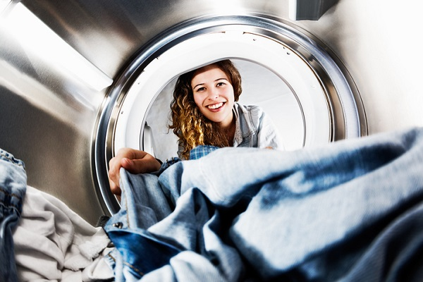 Smiling blonde beauty loads her tumble dryer: seens from inside